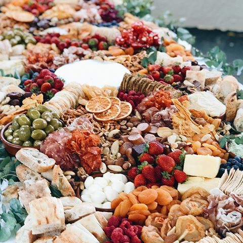 a lush grazing table with charcuterie, cheese, berries and fruits, olives and nuts