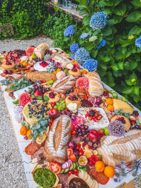 a luxurious grazing table with berries, cheese, veggies and fruit and even some blooms for decor