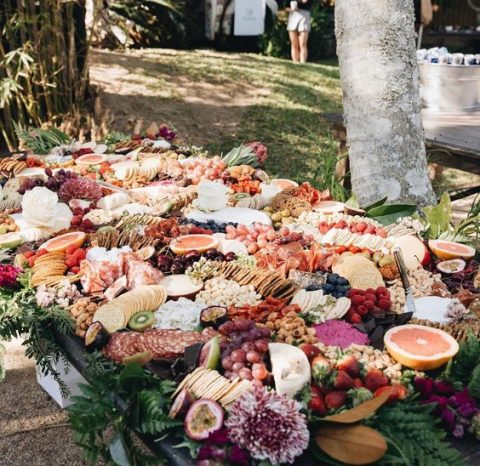 a luxurious grazing table with cheese, charcuterie, berries and fruit plus blooms and greenery