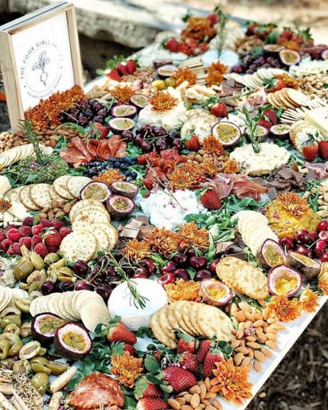 a luxurious grazing table with crackers, cheese, some proschiutto and various kinds of fruit and berries