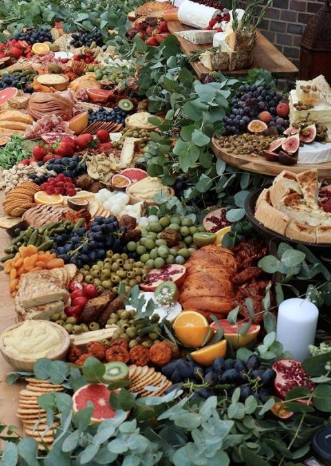 a mouthwatering grazing table with cheese, olives, bread, dips, fruit and candles and eucalyptus for decor