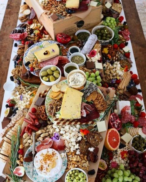 a multi-layer wedding grazing table with everything from cheese and olives to bread and popcorn