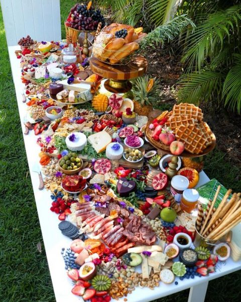 a rich grazing table with charcuterie, cheese, bread and waffles, berries and fruits plus some spreads