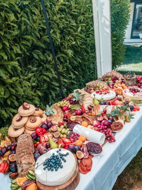 a rich summer grazing table with seasonal fruit and berries, cheese and bread and even bagels