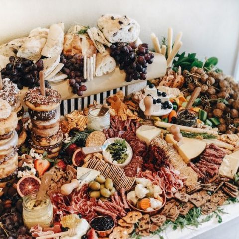 a small yet rich multi-layer grazing table with much bread and charcuterie, cheese, berries and fruit plus glazed donuts on sticks