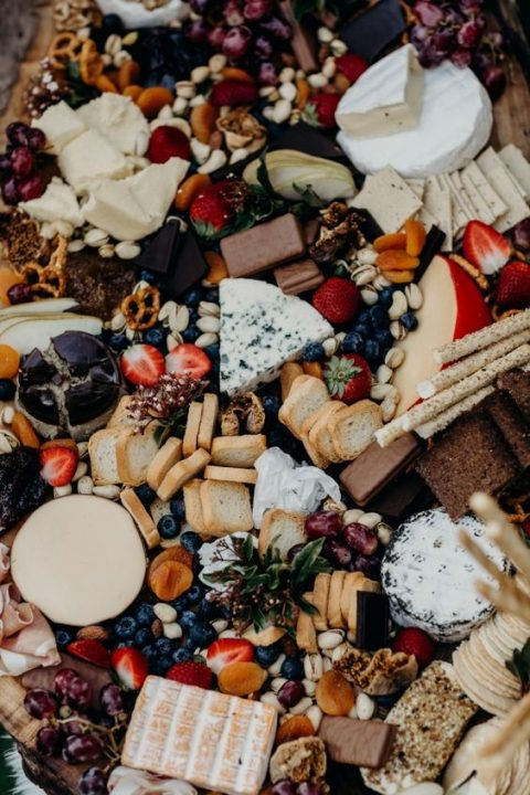 an epic grazing table with cheese, fruits, berries, bread, crackers and nuts and chocolate