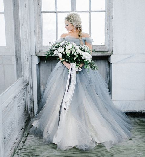 a beautiful and romantic off the shoulder grey tulle wedding ballgown with statement earrings and a train