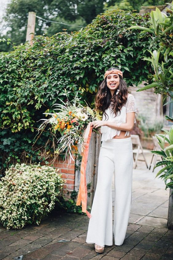 a boho 70s inspired bridal look with a lace crop top, fringe and short sleeves and plain fit and flare pants