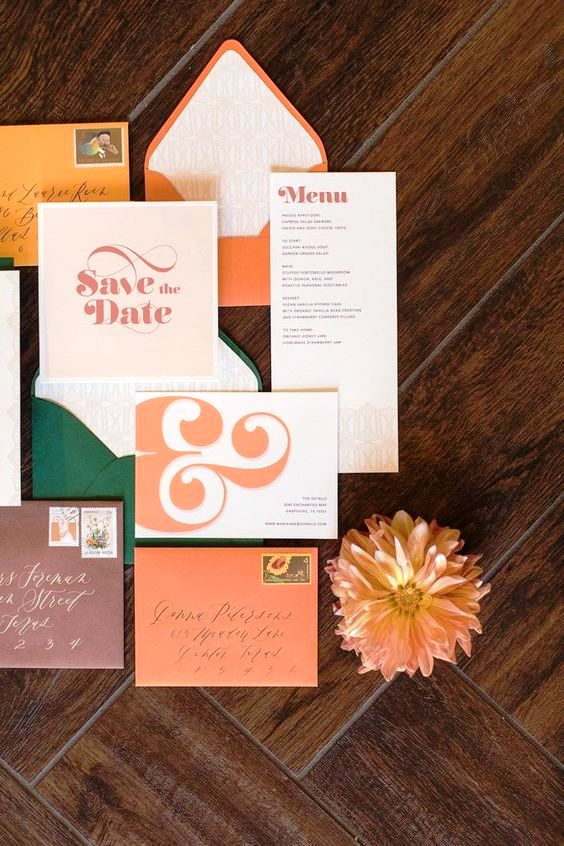 a bright 70s inspired wedding invitation suite in orange, mustard, rust, burgundy and dark green