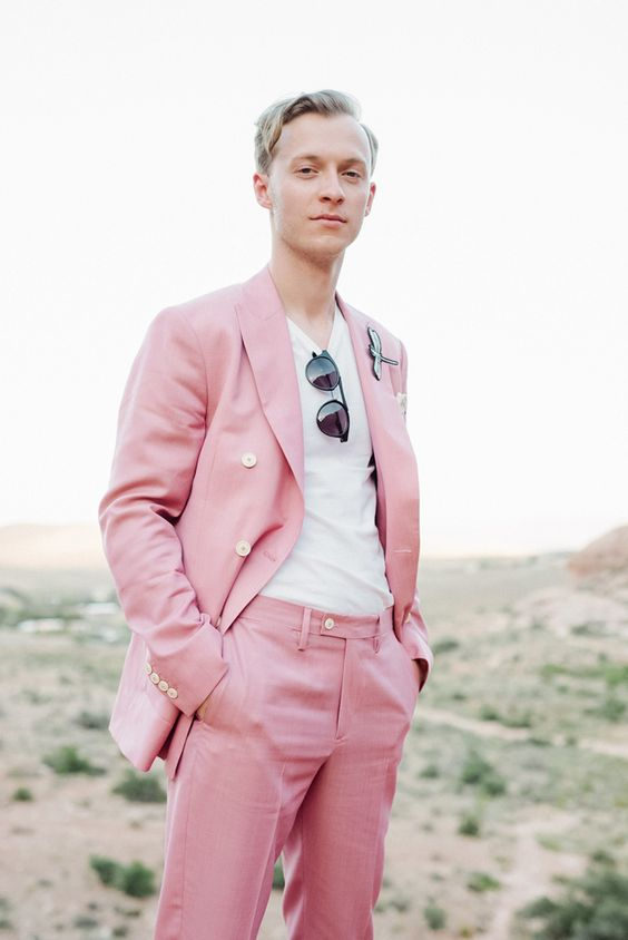 a bright pink groom's suit with a white t-shirt, sunglasses and a unique boutonniere for an offbeat wedding