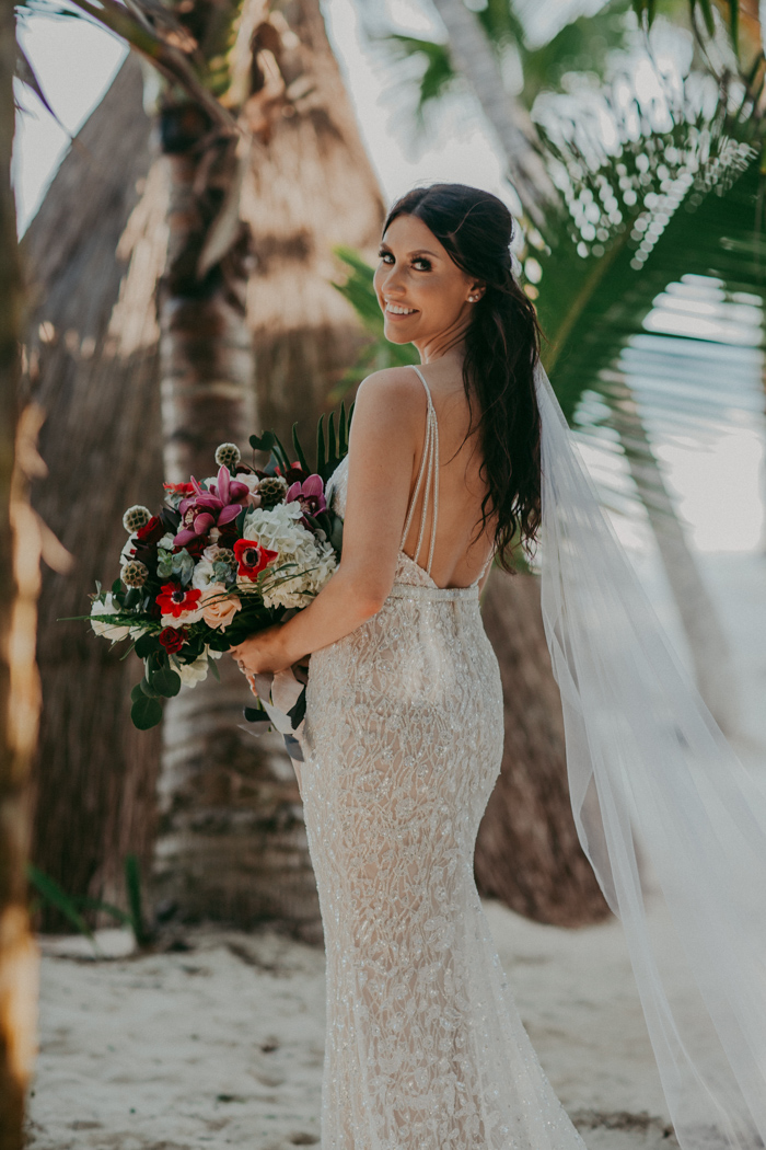 Her bouquet was done with pink, red and white blooms and much greenery