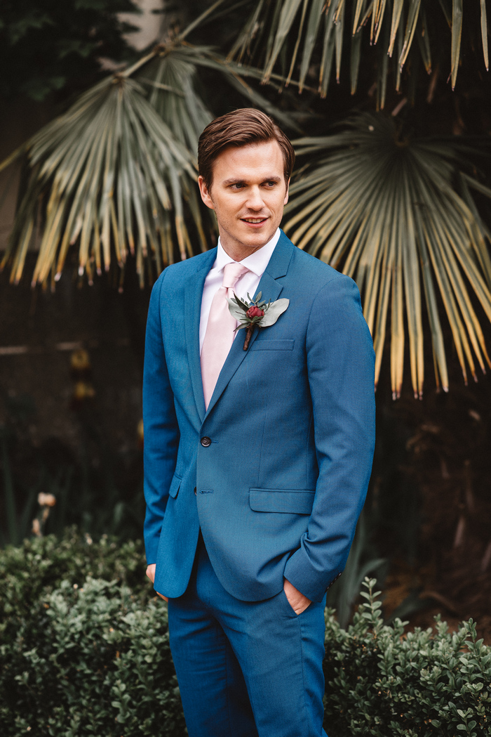 One groom was rocking a stylish blue suit with a pink bow tie and a burgundy boutonniere