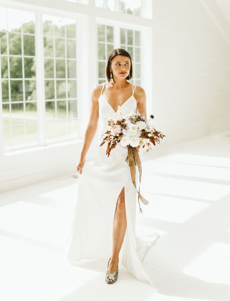The bride was wearing a sleek minimalist wedding dress, bold printed shoes, statement earrings and a sleek bob