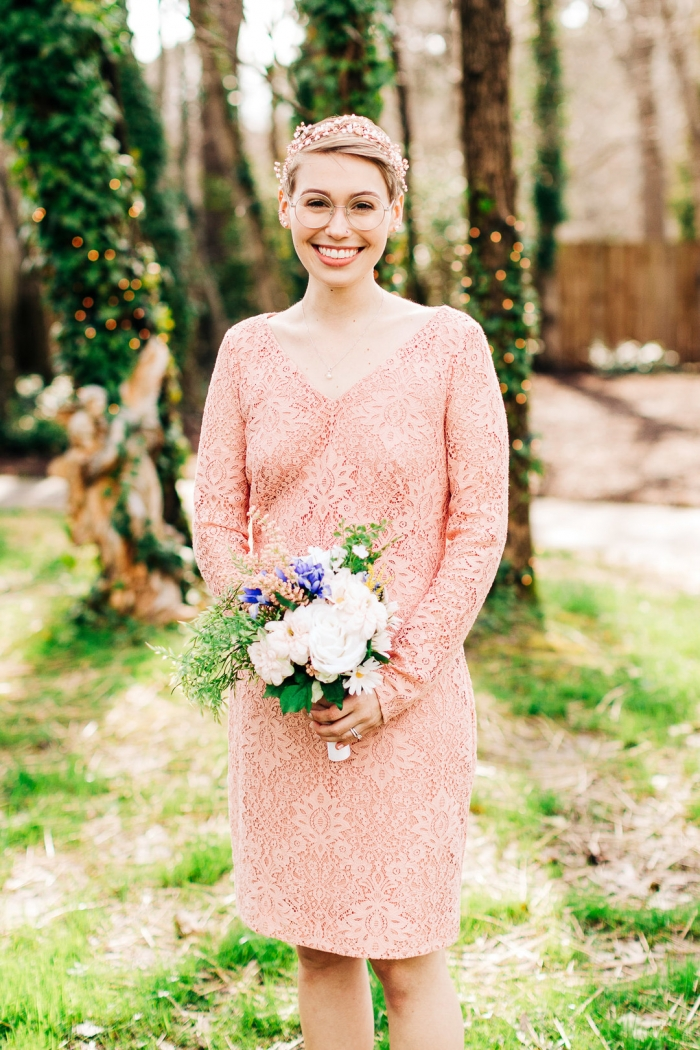 The bride was wearing a pink lace knee wedding dress with long sleeves and a V-neckline