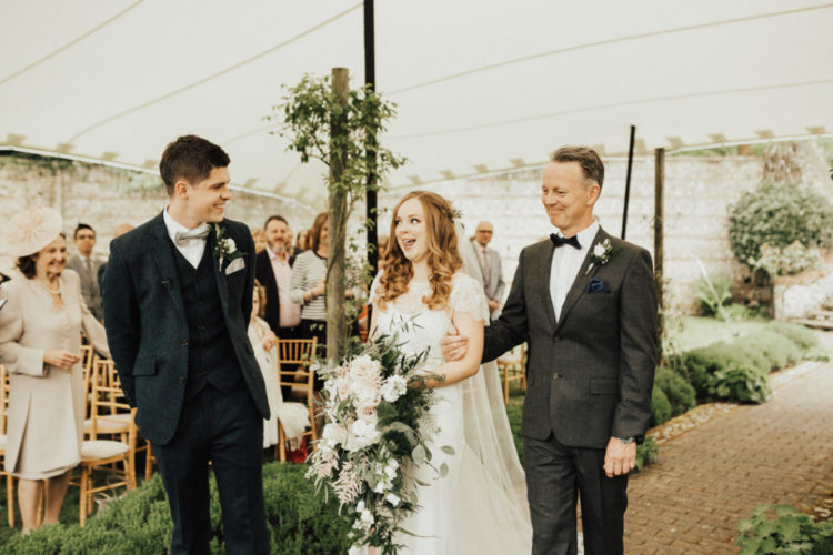 The groom was wearing a navy three-piece wedding suit with a neutral bow tie