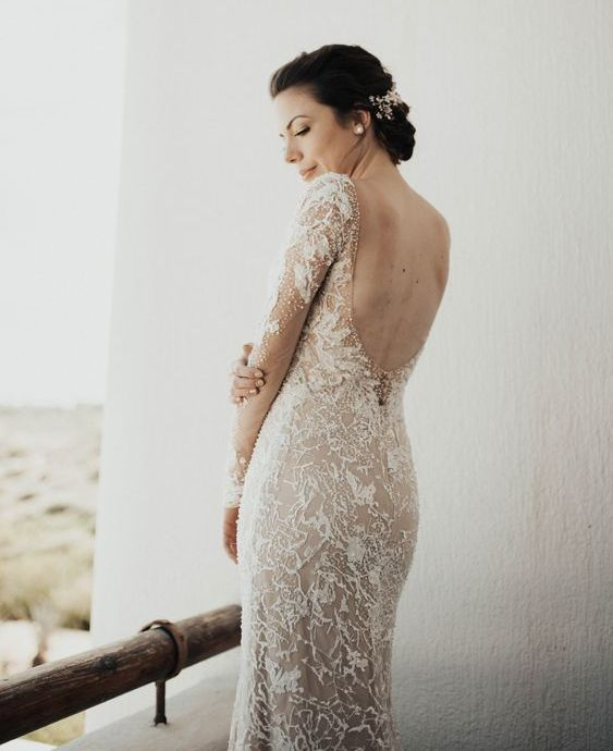 a beautiful lace sheath wedding dress with embellishments, long sleeves and a cutout back plus a train
