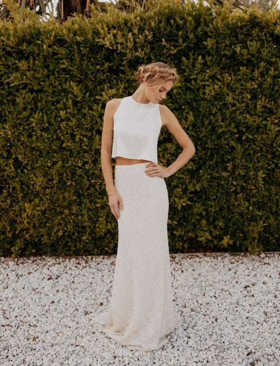 a casual bridal look with a white sleeveless crop top, a neutral lace sheath skirt with a train