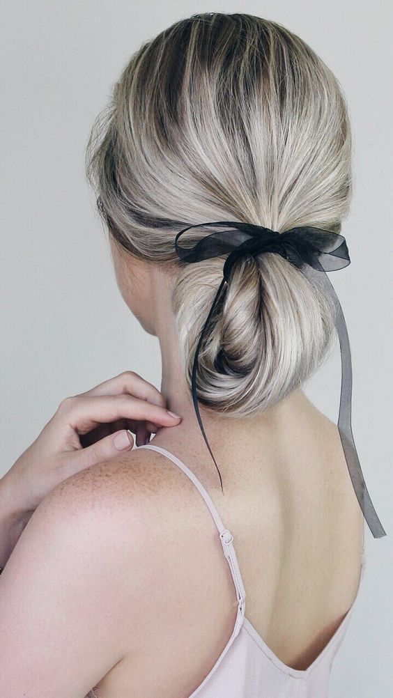 a twisted long and low ponytail turned into a low updo with an ethereal and sheer black ribbon for an accent without much drama