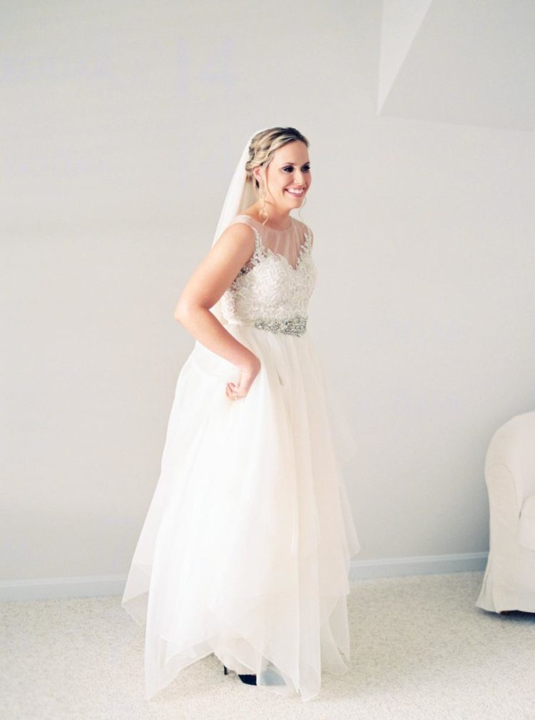 The bride was wearing a wedding separate of a lace top and a layered tulle skirt plus an embellished sash