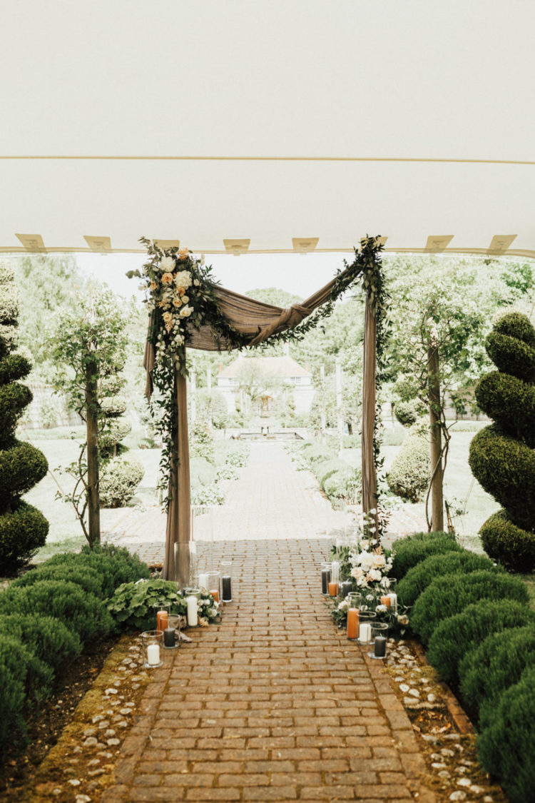 The wedding arch was decorated with burlap, blooms, greenery and with candles on the ground