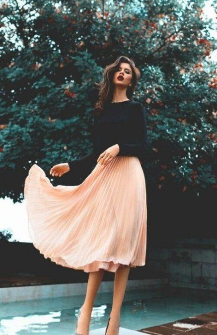 a black long sleeve top, a pink pleated midi skirt and a pair of printed shoes for a sumer wedding guest look