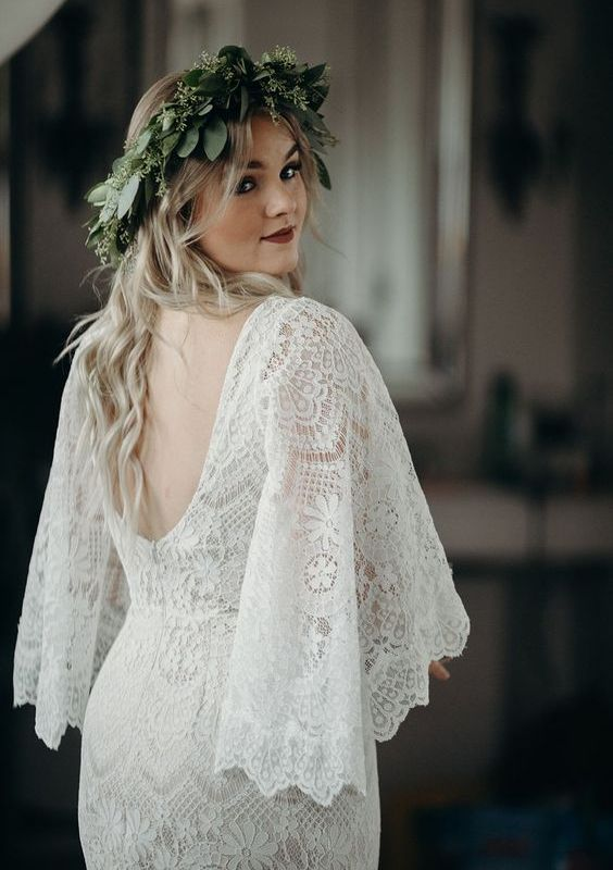 a boho lace sheath wedding dress with bell sleeves and a cutout back with a greenery crown are a gorgeous idea for a boho bride