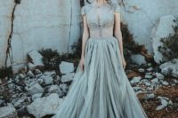 04 a chic and beautiful grey wedding dress with a sheer bodice with lace appliques and a tulle skirt with a train