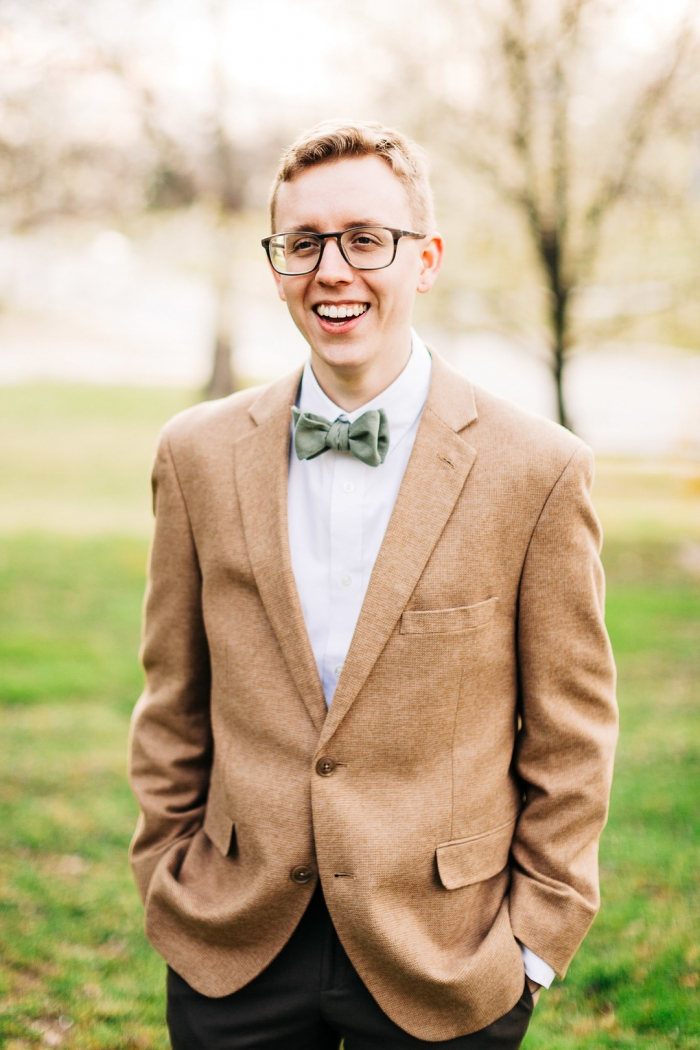 The groom was wearing brown pants, a white shirt, a tan jacket and a green bow tie