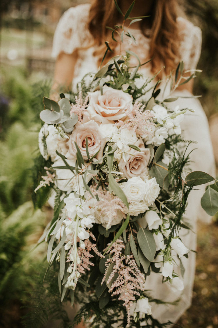 The wedding bouquet was lush and neutral, with blush and white blooms and cascading greenery