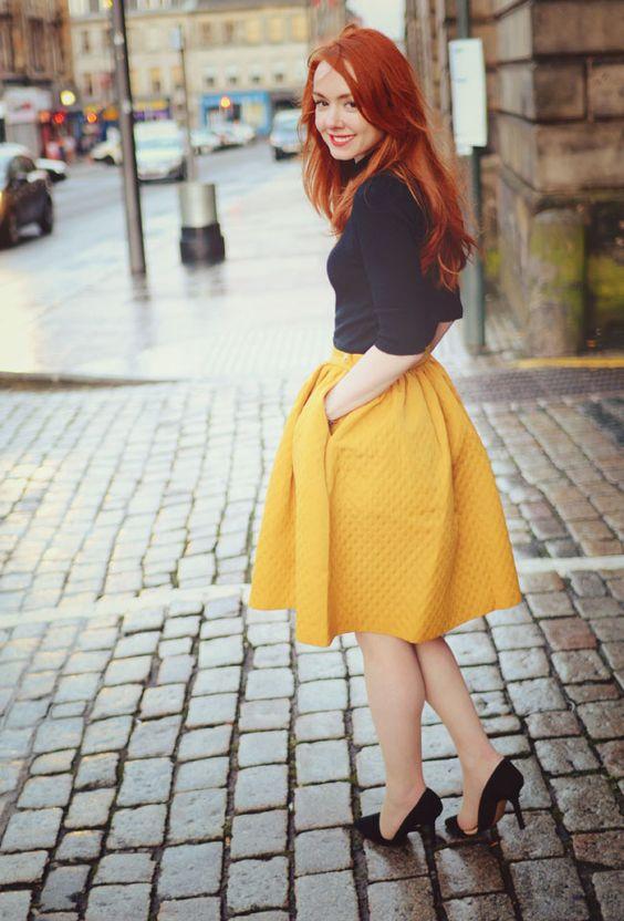 a black turtleneck with short sleeves, a full marigold knee skirt, black heels for a bold and chic fall outfit