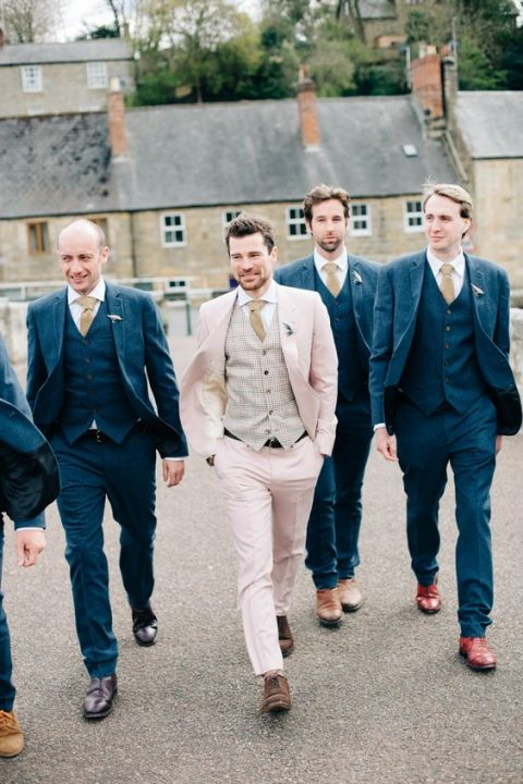 a blush groom's suit with a checked waistcoat, a beige tie and brown shoes is a non traditional and chic idea