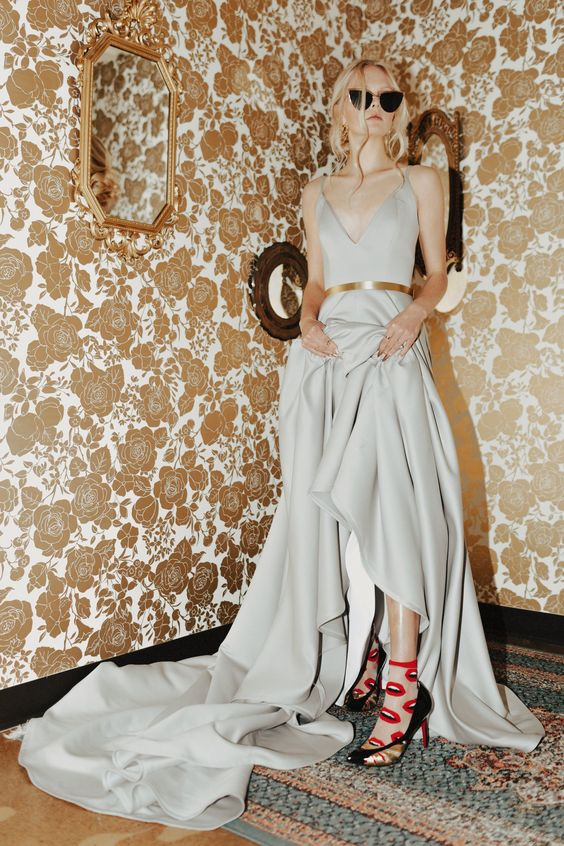 a dove grey A-line wedding dress with a deep neckline, a shiny belt and catchy shoes with socks
