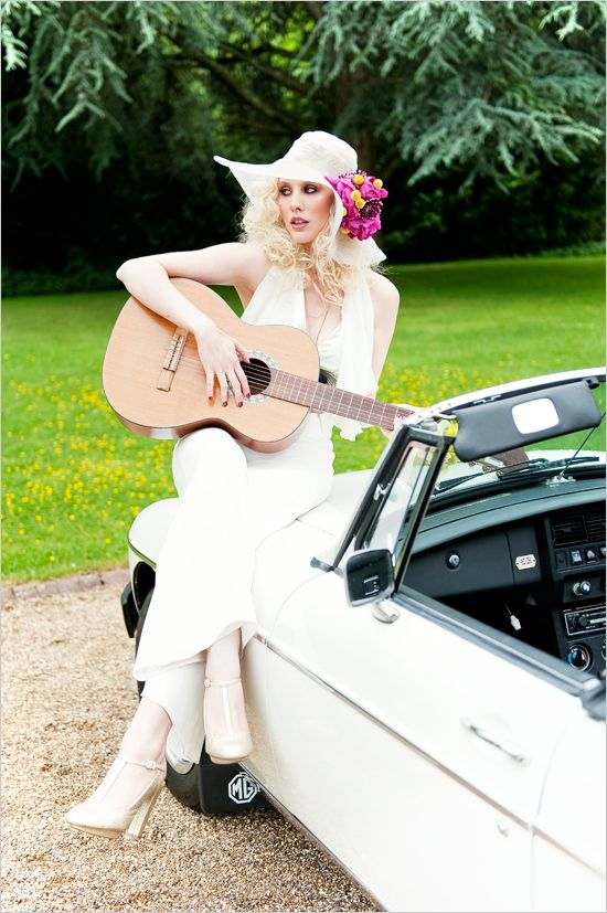 a white sleeveless bridal jumpsuit, white shoes and a matching hat accented with a bright flower