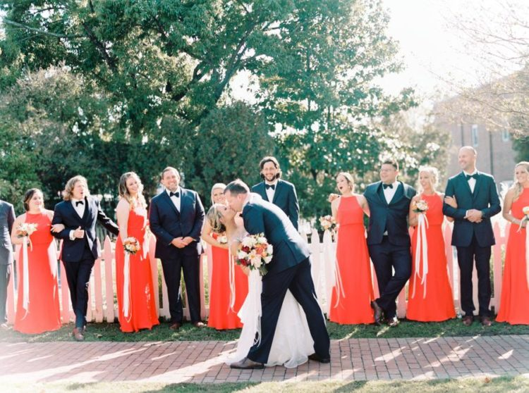 The groom and groomsmen were rocking navy tuxedos and the bridesmaids were rocking sleeveless red maxi dresses