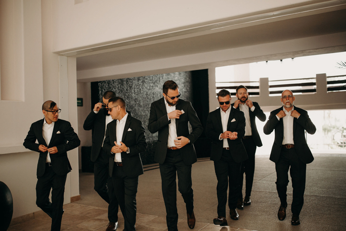 The groom and groomsmen were wearing black suits and white shirts plus brown shoes