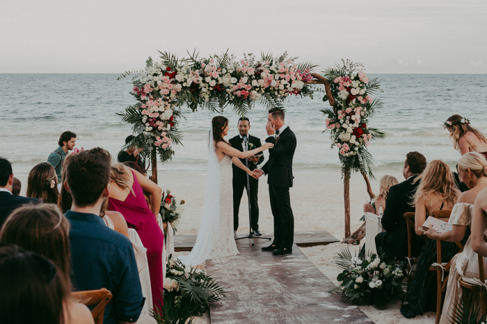 The wedding arch was done with pink, blush, white blooms and much tropical greenery, and the ocean was the backdrop