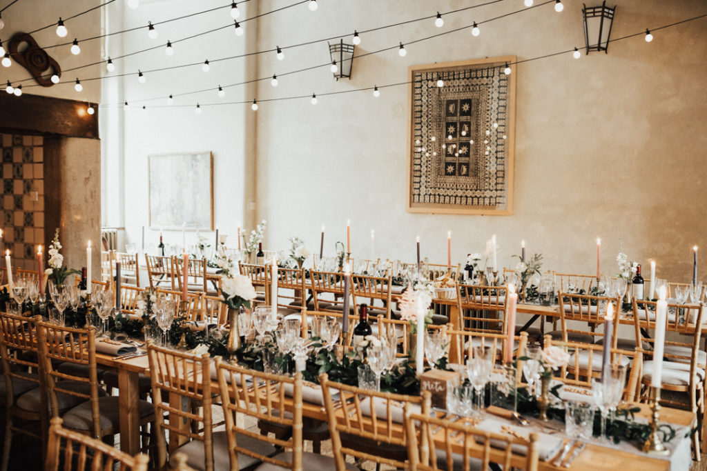 The wedding venue was all lit up, with lots of greenery and neutral blooms