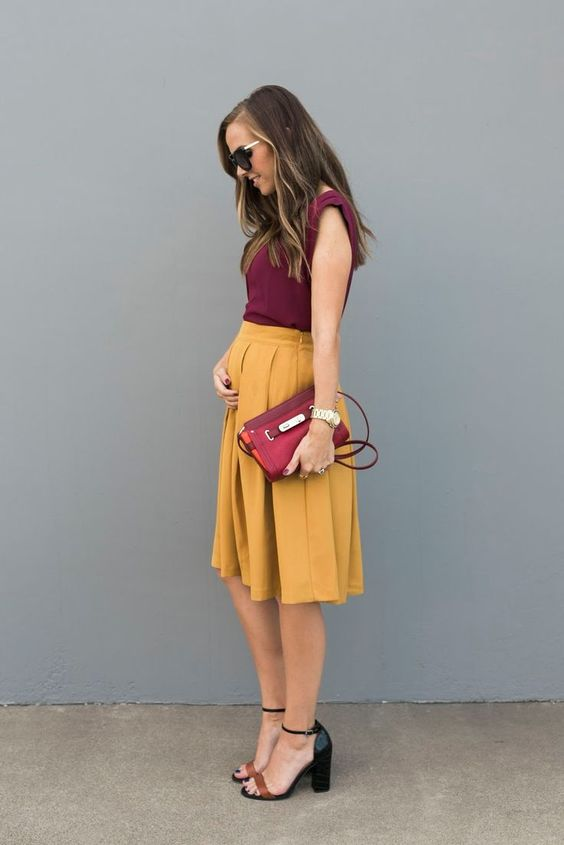 a burgundy top with no sleeves, a marigold knee pleated skirt, a burgundy clutch and two tone block heels