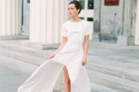 06 a casual plain maxi wedding dress with short sleeves, a high neckline, a front slit and blue heels plus statement earrings