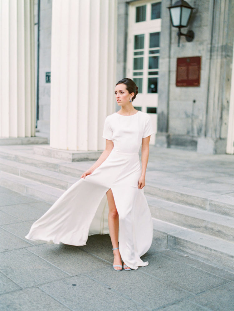 a casual plain maxi wedding dress with short sleeves, a high neckline, a front slit and blue heels plus statement earrings