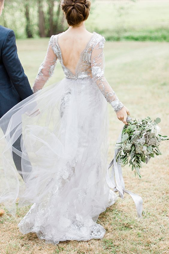 a dove grey wedding dress of lace, with long sleeves, a cutout back and a train for a slight touch of color