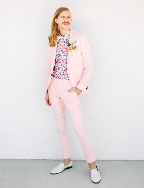 a fun pink groom's suit, a bright floral shirt, a pink bow tie and white moccasins for a whimsy wedding