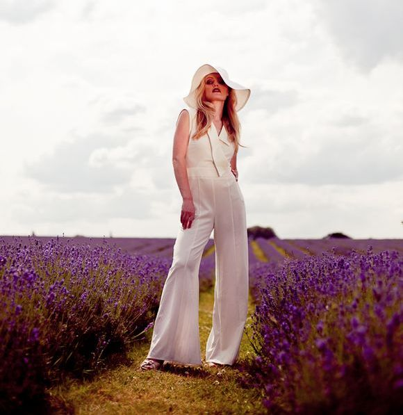 a white jumpsuit with no sleeves and fit and flare pants plus a chic hat for a 70s bridal look