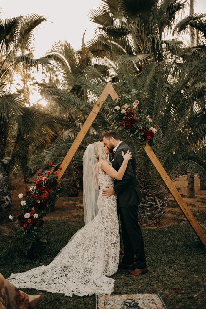 The triangular wedding arch was decorated with lush florals in red and neutrals and greenery