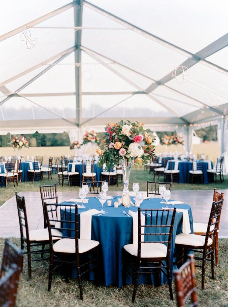 The wedding tablescapes were done with navy tablecloths, bright and textural florals and candles