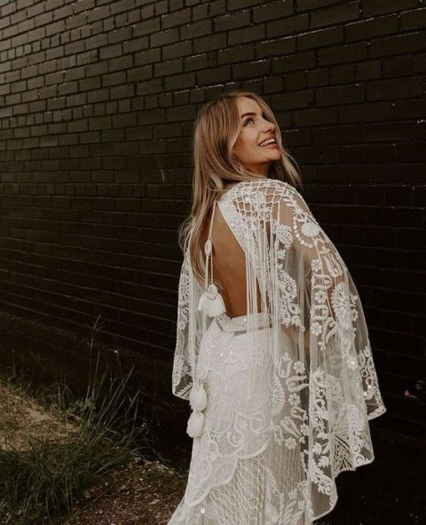 a boho lace wedding gown with wide bell sleeves, a cutout back and tassels on long ties for a glam boho bride