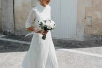 07 a casual wedding look with a neutral plain turtleneck top and a pleated white midi plus gold shoes