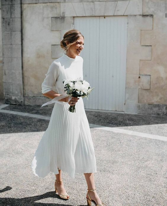 a casual wedding look with a neutral plain turtleneck top and a pleated white midi plus gold shoes