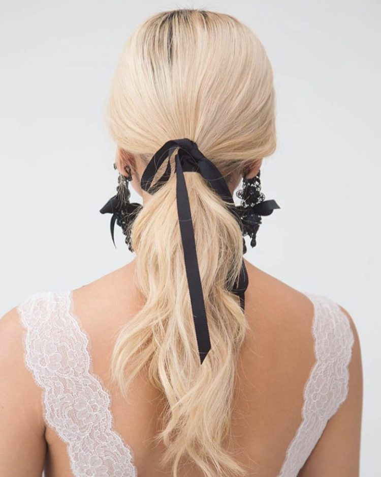a wavy ponytail with a black ribbon and matching black lace and ribbon earrings by Marchesa