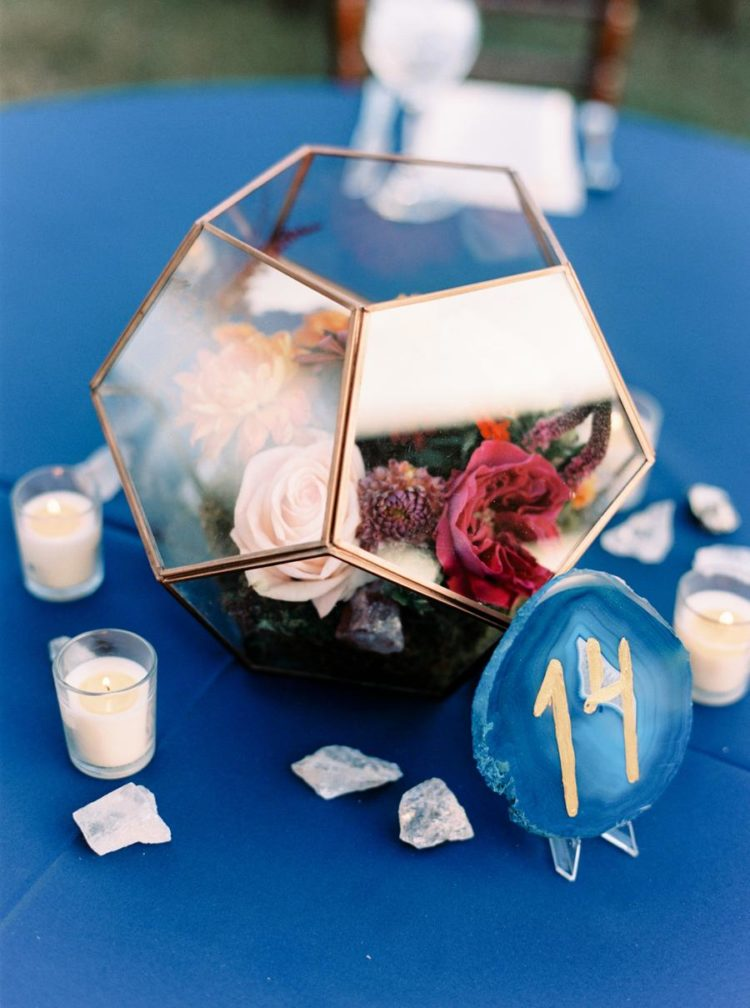 Pretty terrariums with bright blooms, agates, table numbers and candles were used to decorate the tables
